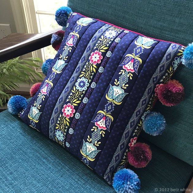 Pompom accent pillow on chair Betz White